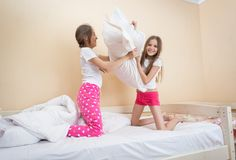 Two teenage sister sitting on bed and having pillow fight. Two teen sister sitting on bed and having pillow fight Royalty Free Stock Images