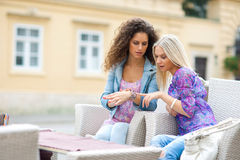 Two teen woman friends having fun in outdoor cafe Royalty Free Stock Photography