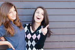 Two pretty happy Teen Girl Friends Laughing & pointing to copyspace. Two Teen young women happy laughing pointing to copyspace, dressed for spring or autumn Royalty Free Stock Image