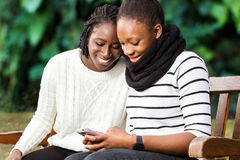 Two teenage african girlfriends socializing on phone. Close up portrait of two african american teenage girlfriends socializing on smart phone. Girls sitting on Royalty Free Stock Images
