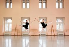 Two teenage ballerinas practicing in large classical ballet studio royalty free stock photo