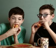 Two teenage boy eating hot dog in fast food restaurant. Close up photo royalty free stock photos