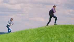 Two teenage boys bang one after another over a beautiful green hill against a blue sky with clouds stock footage