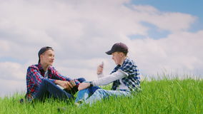 Two teenage boys communicate in nature. They sit on a green meadow, use telephones. Against the background of a. Beautiful sky. HD video stock video footage