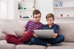 Two teenage boys with gadgets on couch at home Stock Photography