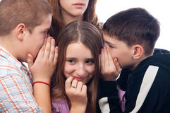 Two teenage boys and girl gossiping Royalty Free Stock Photo