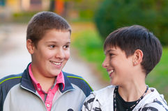 Two teenage boys laughing and kidding in park. Two teenage boys laughing and kidding in the park on beautiful autumn day Royalty Free Stock Photo