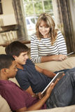 Two Teenage Boys And Mother Sitting On Sofa At Home Using Tablet Computer stock images