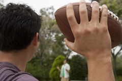 Two teenage boys (17-19) playing american football in park, focus on foreground, close-up, rear view Royalty Free Stock Images