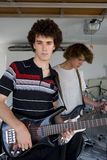 Two teenage boys (15-17) playing electric guitar, portrait of boy in foreground Stock Photography