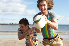 Two Teenage Boys Playing Rugby On Beach. Together Royalty Free Stock Images