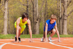 Two teenage boys ready to start running on a track Royalty Free Stock Photography