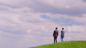Two teenage boys run to a green hill or mountain. Happy childhood, the energy of youth stock footage