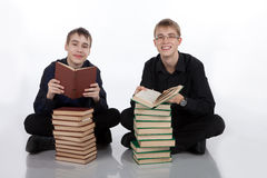 Two teenage boys sitting on a floor with books Stock Images