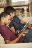 Two Teenage Boys Sitting On Sofa At Home Using Tablet Computer And Laptop Stock Photography