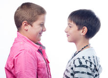 Two teenage boys smiling at each other isolated on white Royalty Free Stock Photography