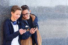 Two teenage boys standing together near the wall outdoors, and looking at mobile phone stock photos