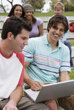Two teenage boys (17-19) using laptop, smiling, teenage girls watching in background Stock Images