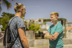 Two teenage brothers or friends standing chatting Royalty Free Stock Photo