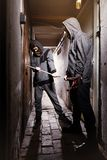 Teenage thieves breaking into the basement property with bolt cutters. Two teenage burglars breaking in basement cellar with 30 inch bolt cutters Royalty Free Stock Photos
