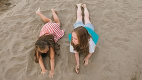 Two teenage children are lie on the beach. Two teenage are lie on a sandy beach near the sea. Girl playing, talk to each other. Sisters are dressed in dresses Royalty Free Stock Image