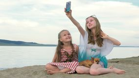 Two teenage children are sitting on the beach in phone. Two teenage children are sitting on the beach. They wear sunglasses. Sisters communicate with each other stock video
