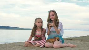 Two teenage children are sitting on the beach in phone. Two teenage children are sitting on the beach. They wear sunglasses. Sisters communicate with each other stock footage