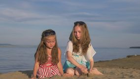 Two teenage children are sitting on the beach. They wear sunglasses, they play with sand. Kid indulge. Sisters communicate with each other stock video footage