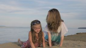 Two teenage children are sitting on the beach. They wear sunglasses, they play with sand. Kid indulge. Sisters communicate with each other stock footage