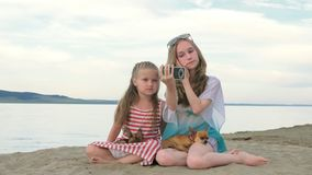 Two teenage children are sitting on the beach in phone. Two teenage children are sitting on the beach. They wear sunglasses. Sisters communicate with each other stock video footage