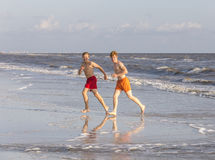 Two teenage friends and brothers enjoy jogging along the beach Royalty Free Stock Photo