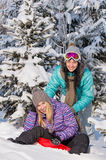 Two teenage friends enjoy winter snow bobsleigh Stock Images
