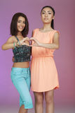Two teenage friends in studio. Two teenage friends forming heart shape in studio Royalty Free Stock Photos