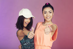 Two teenage friends in studio, giving thumbs up Royalty Free Stock Photos