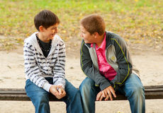 Two teenage friends talking in the park stock images