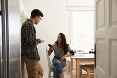 Two teenage friends using smartphones, talking in kitchen Stock Photography