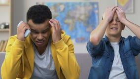 Two teenage friends watching sports on tv, favorite team losing, upset fan boys