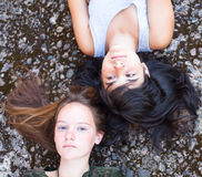 Two teenage girl friends lying on a granite background Royalty Free Stock Images