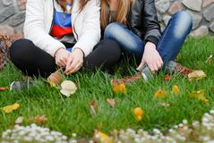 Two teenage girl friends sitting on green grass Stock Photo