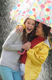 Two Teenage Girl Sheltering From Rain Beneath Umbrella. Smiling Stock Image