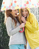 Two Teenage Girl Sheltering From Rain Beneath Umbrella. Smiling To Camera Royalty Free Stock Images
