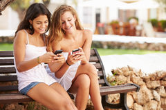 Two Teenage Girl Using Mobile Phone Sitting On Park Bench Royalty Free Stock Photo