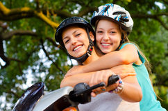 Two teenage girlfriends riding scooter Stock Photo