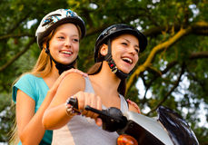 Two teenage girlfriends riding scooter Stock Photos