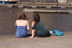Two teenage girls. Two beautiful teenage girls sitting beside a dock Royalty Free Stock Photos
