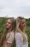 Two teenage girls back to back Stock Photo