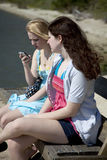 Two Teenage Girls on Bench with Cell Phone. Two white teenage girls sitting on a bench, one fifteen, one eighteen.  Eighteen-year-old is reviewing a text message Royalty Free Stock Photo