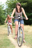 Two teenage girls on bikes. In the forest Royalty Free Stock Photography