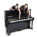 Two teenage girls and black upright piano. In studio against white background Stock Photos