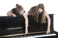 Two teenage girls and black upright piano. In studio against white background Royalty Free Stock Photo